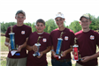 Four youth holding trophies from shooting competition