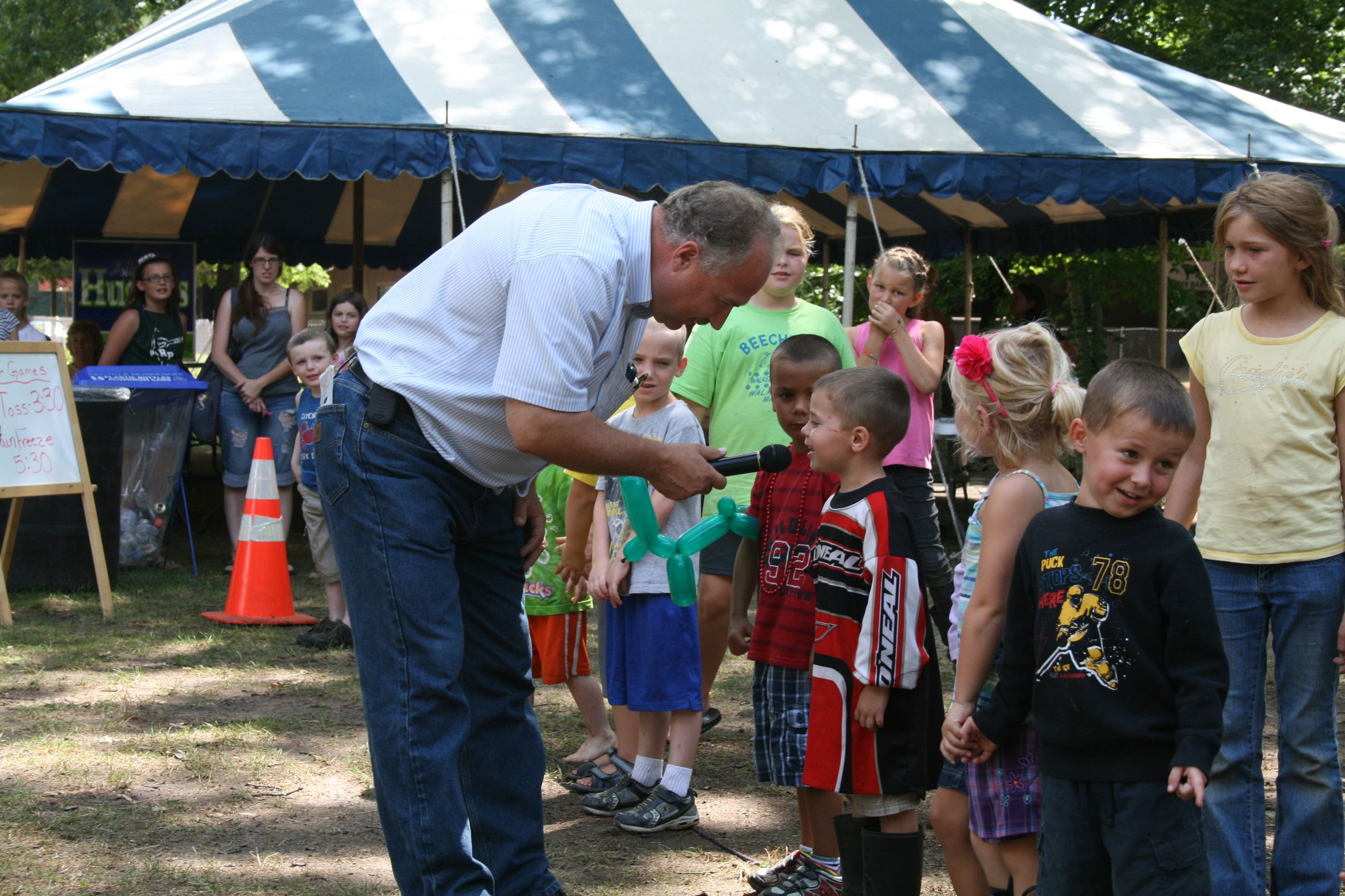 Image of older man talking with children at the fair