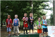 Six children standing on podiums with medals