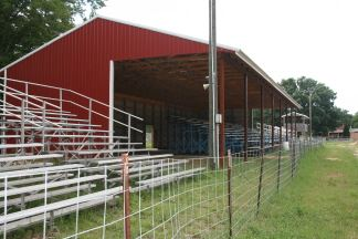 Image of bleachers and a red pole barn